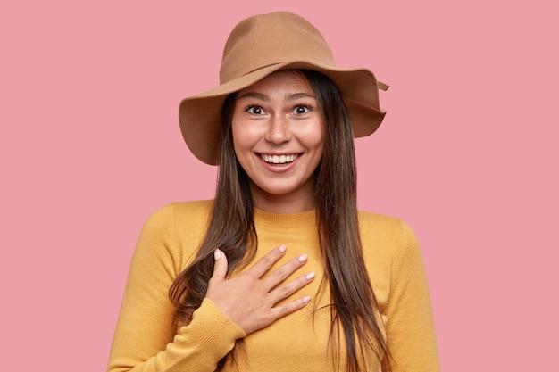 Emocjonalnie zaskoczona piegowata kobieta z pozytywnym wyrazem twarzy trzyma rękę na piersi, szeroko uśmiecha się do kamery