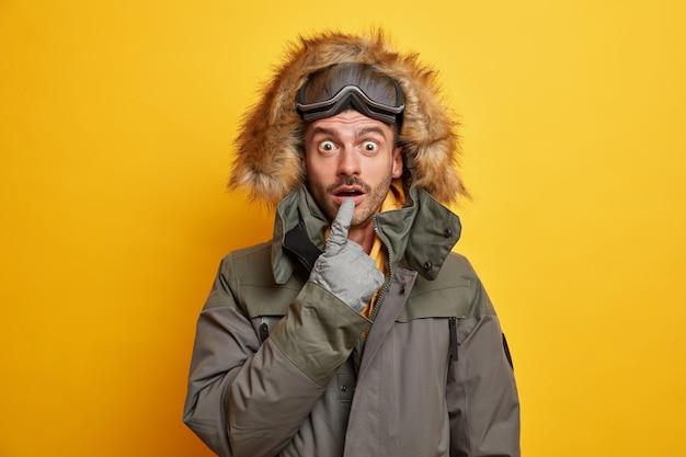 Emocjonalnie zaskoczony snowboardzista trzyma usta otwarte przed cudem odpoczywa w górach lubi sporty zimowe nosi ciepłą kurtkę z futrzanym kapturem jeździ na nartach.