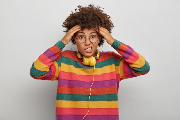 Emocjonalnie zdziwiona młoda afroamerykanka trzyma obie ręce na głowie, marszczy brwi i patrzy z niezadowoleniem, cierpi na ból głowy