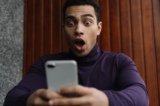 Emocjonalny afroamerykanin mężczyzna trzyma telefon komórkowy, robi zakupy online, gra w gry wideo