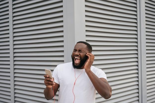 Emocjonalny afroamerykanin słuchanie muzyki na świeżym powietrzu, śpiewając piosenkę