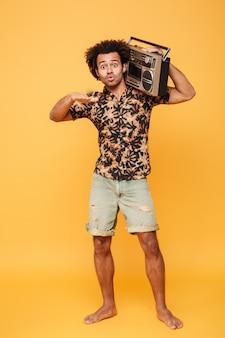 Emocjonalny afrykański mężczyzna stojący z magnetofonem