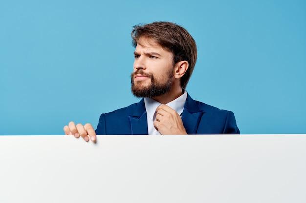 Emocjonalny biznesmen zerkając zza banera przycięty widok niebieski