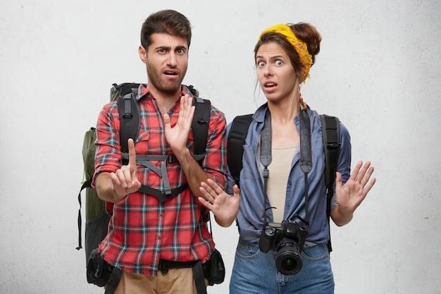 Emocjonalny brodaty facet i piękna kobieta z profesjonalnym aparatem, gestykuluje obiema rękami, robi znak stopu, wyraża odmowę, odrzucenie, niechęć. ludzkie emocje i uczucia