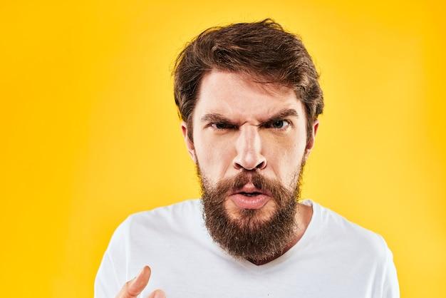 Emocjonalny brodaty mężczyzna gestykuluje z agresją rąk niezadowolony szczegół żółtym tle