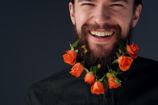Emocjonalny brodaty mężczyzna kwiaty romans zbliżenie ciemne tło. wysokiej jakości zdjęcie