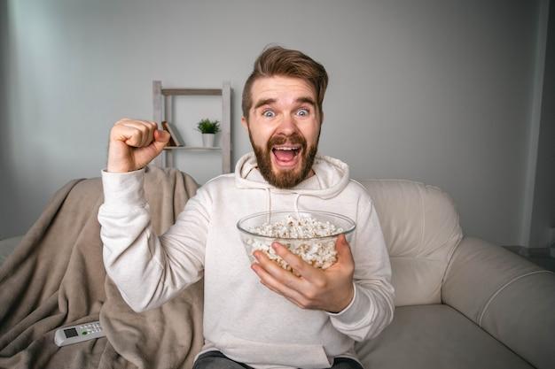 Emocjonalny brodaty mężczyzna ogląda kanały sportowe w telewizji, wspierając drużynę w domu, fan sportu i