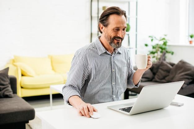 Emocjonalny brodaty mężczyzna siedzi przy stole z filiżanką kawy i uśmiecha się, patrząc na ekran nowoczesnego laptopa