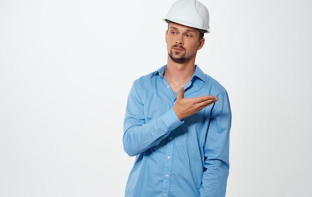 Emocjonalny budowniczy architekt w białym kasku i niebieskiej koszuli na na białym tle.