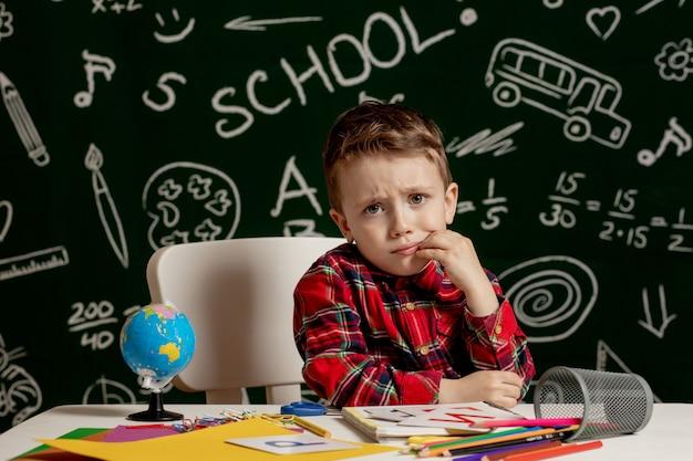 Emocjonalny chłopiec siedzący na biurku z wieloma przyborami szkolnymi. pierwszy dzień szkoły. mały chłopiec ze szkoły podstawowej. powrót do szkoły. dziecko ze szkoły podstawowej.