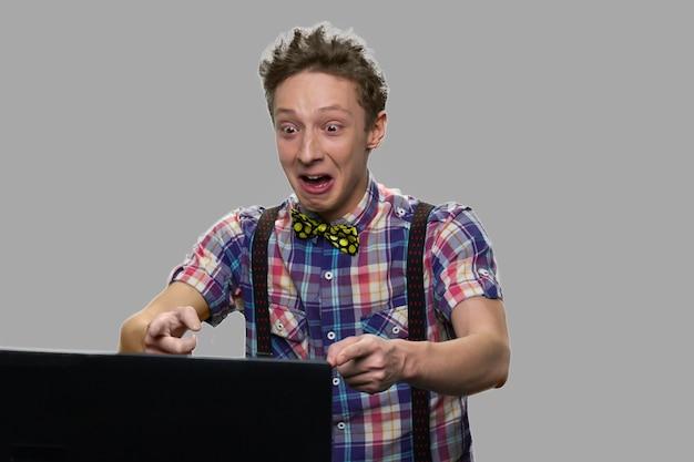 Emocjonalny chłopiec teen patrząc na ekran laptopa. ekspresyjny zszokowany nastolatek facet za pomocą komputera typu tablet na szarym tle.