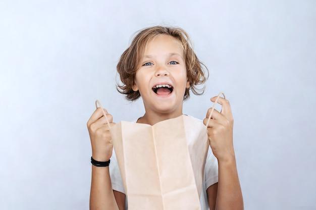 Emocjonalny chłopiec z papierową torbą na świetle