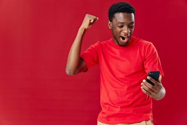 Emocjonalny człowiek afrykański wygląd z telefonem w ręce technologia komunikacji radość. zdjęcie wysokiej jakości