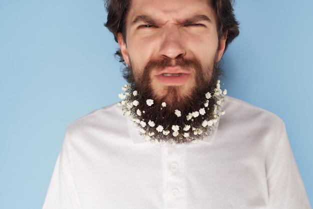 Emocjonalny człowiek w białej koszuli kwiaty w broda ozdoba przycięty widok. zdjęcie wysokiej jakości