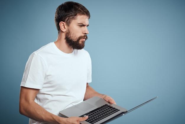 Emocjonalny człowiek z laptopem w ręce na modelu internet klawiatury niebieski monitor