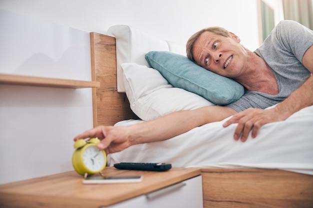 Emocjonalny Dojrzały Mężczyzna Rozciągający Rękę, Gdy Zamierza Przestać Denerwujący Dźwięk W Sypialni Premium Zdjęcia