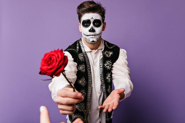 Emocjonalny facet sięga po ukochaną. portret mężczyzny z pomalowaną twarzą w meksykańskiej kamizelce z różą w dłoniach.