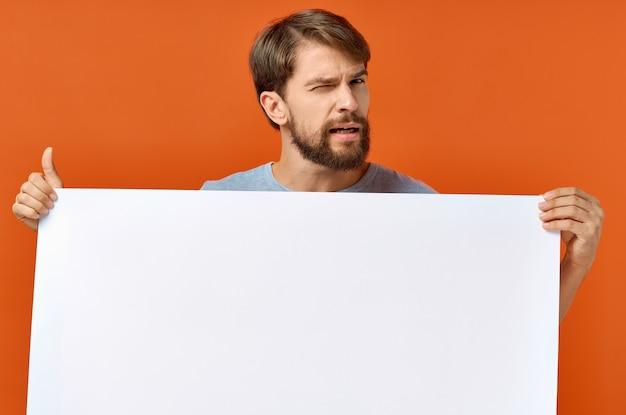 Emocjonalny facet trzymający w rękach białą kartkę papieru plakat reklamowy makieta. wysokiej jakości zdjęcie