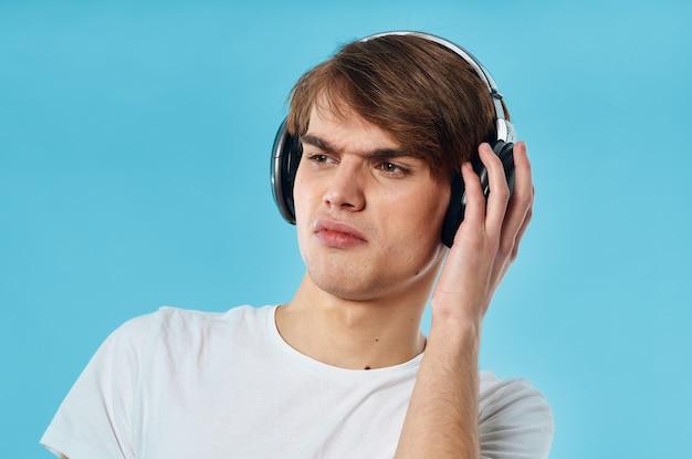 Emocjonalny facet w białej koszulce noszącej słuchawki muzyczne moda