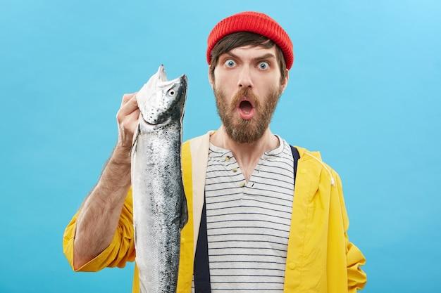 Emocjonalny facet w czerwonym kapeluszu i żółtym płaszczu przeciwdeszczowym, trzymając w ręku ogromne długie ryby morskie