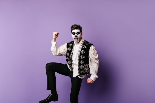 Emocjonalny facet w meksykańskich ubraniach raduje się ze zwycięstwa. zdjęcie mężczyzny z maską czaszki pozowanie na liliowej ścianie.