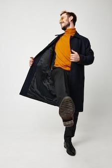 Emocjonalny facet w modnych ciuchach czarny płaszcz spodnie pomarańczowy sweter. wysokiej jakości zdjęcie