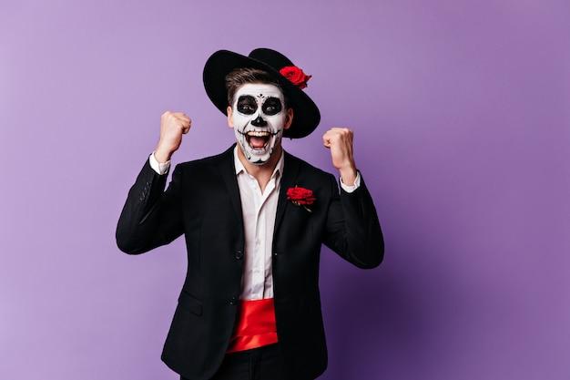 Emocjonalny facet w niezwykłym meksykańskim stroju na maskaradzie krzyczy radośnie, ciesząc się ze zwycięstwa.