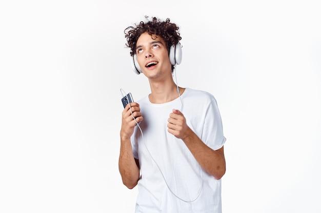 Emocjonalny facet z kręconymi włosami w słuchawkach do słuchania muzyki