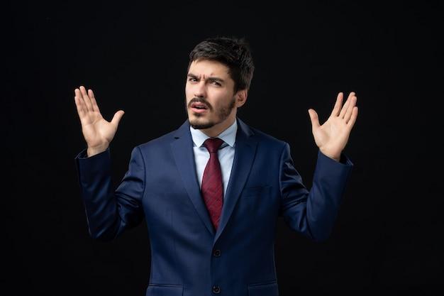 Emocjonalny i młody brodaty mężczyzna pozuje ze zdezorientowanym wyrazem twarzy na izolowanej ciemnej ścianie
