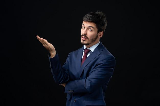 Emocjonalny i młody brodaty mężczyzna pytający o coś na izolowanej ciemnej ścianie