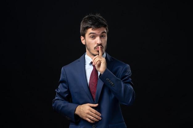 Emocjonalny i młody brodaty mężczyzna robi gest ciszy na izolowanej ciemnej ścianie