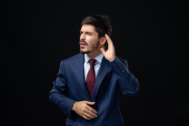 Emocjonalny i młody brodaty mężczyzna słuchający ostatnich plotek na izolowanej ciemnej ścianie