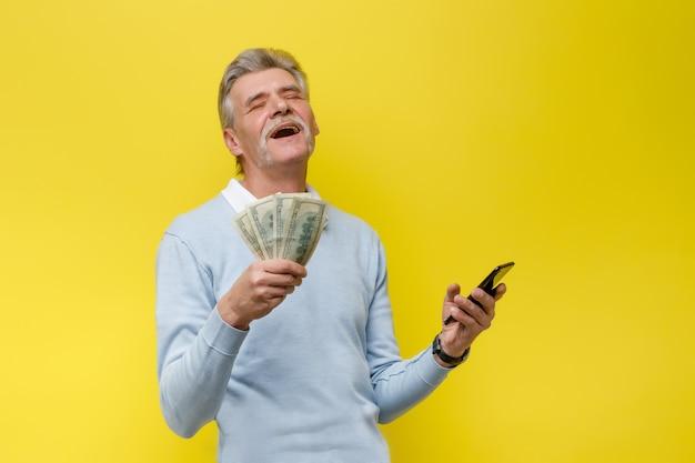 Emocjonalny i szczęśliwy starszy mężczyzna z gotówką na żółtej ścianie
