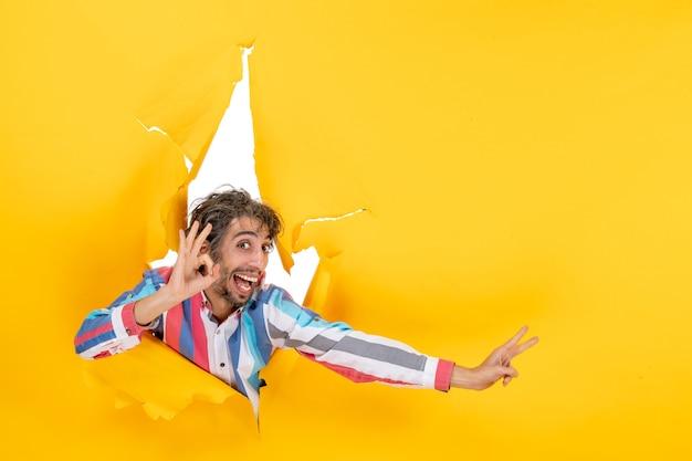 Emocjonalny i uśmiechnięty młody człowiek wykonujący gest okularów pokazujący dwa w rozdartym żółtym tle dziury w papierze