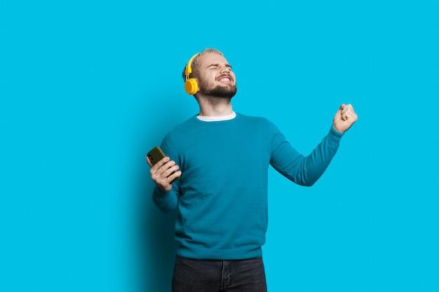 Emocjonalny kaukaski mężczyzna z brodą i blond włosami słucha muzyki na niebieskiej ścianie za pomocą telefonu komórkowego i słuchawek