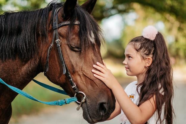 Emocjonalny kontakt z koniem. dziewczyna jeździ konno latem.