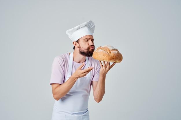 Emocjonalny kucharz z chlebem w dłoniach do pieczenia gotowania