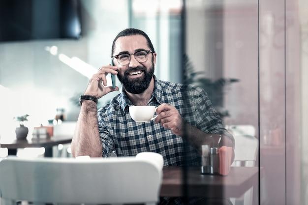 Emocjonalny mężczyzna. brodaty emocjonalny mężczyzna czuje się szczęśliwy dzwoniąc do przyjaciela pijącego kawę w przytulnej stołówce