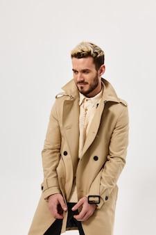 Emocjonalny mężczyzna moda fryzura beżowy płaszcz studio jasne tło