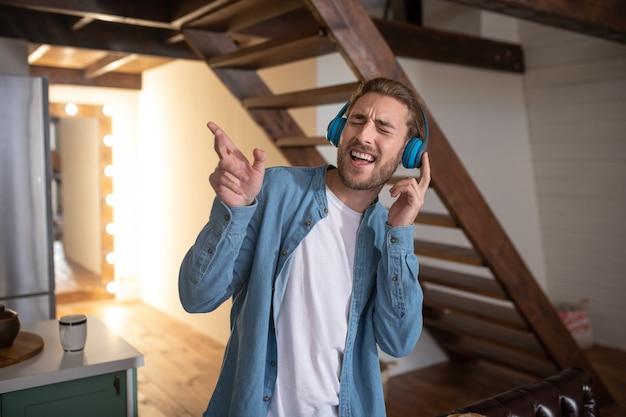 Emocjonalny mężczyzna śpiewa podczas słuchania swojej ulubionej muzyki