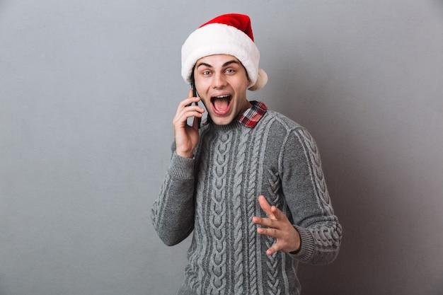 Emocjonalny mężczyzna ubrany w świąteczny santa hat rozmawia przez telefon.
