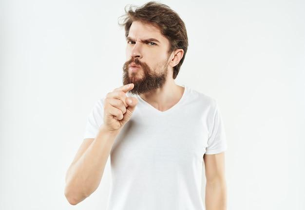 Emocjonalny mężczyzna w białej koszulce gestykuluje gniewne jasne tło