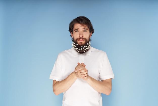 Emocjonalny mężczyzna w białej koszulce kwiaty w niebieskiej brodzie z bliska
