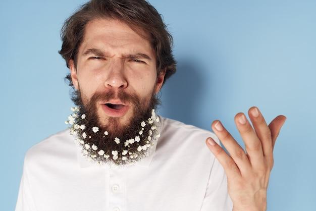 Emocjonalny mężczyzna w białej koszulce kwiaty w zbliżenie brodę na niebieskim tle