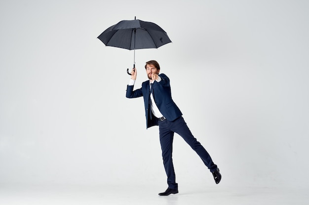 Emocjonalny mężczyzna w garniturze z parasolką w ręku zła pogoda