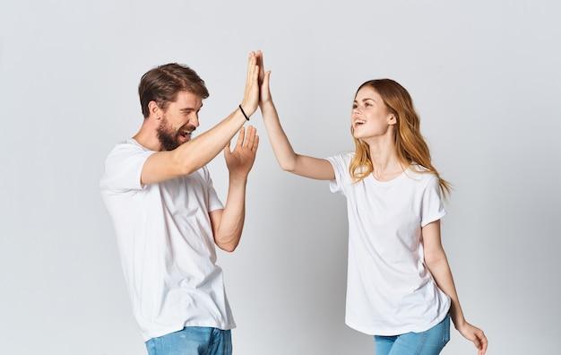 Emocjonalny mężczyzna w koszulce i kobieta w dżinsach na lekkiej tkaninie w stylu mody.