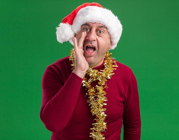 Emocjonalny mężczyzna w średnim wieku ubrany w boże narodzenie santa hat z blichtrem wokół szyi krzycząc ręką w pobliżu ust stojących na zielonym tle