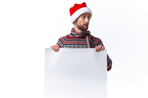 Emocjonalny mężczyzna w świątecznym kapeluszu z białym plakatem makieta boże narodzenie na białym tle