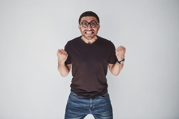 Emocjonalny mężczyzna w zwykłym ubraniu krzyczy z bólu lub ze strachu.