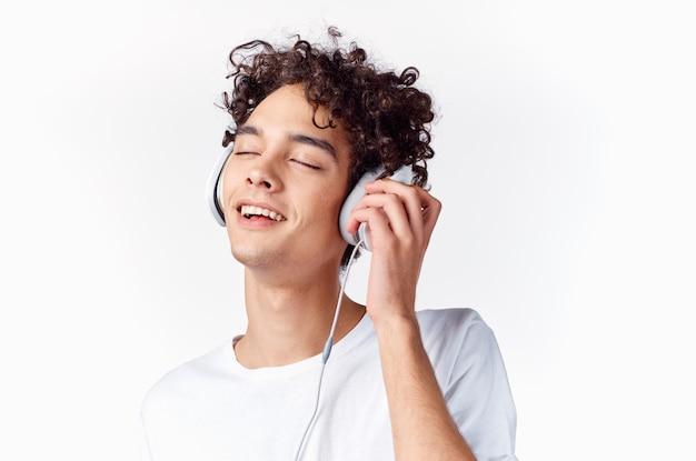 Emocjonalny mężczyzna z kręconymi włosami iw słuchawkach słucha muzyki na jasnym tle